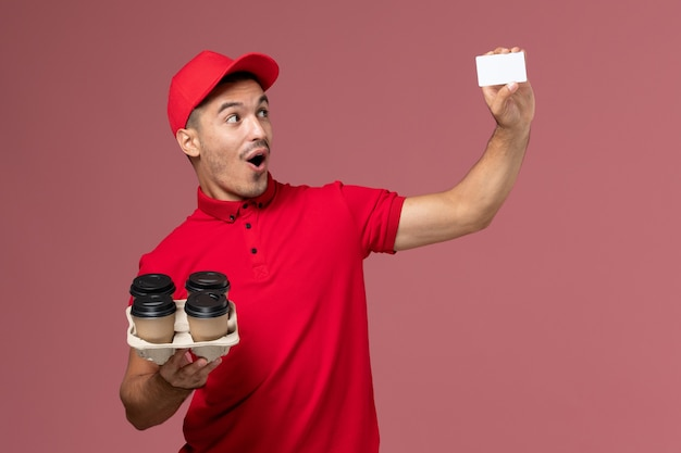 Front view male courier in red uniform holding delivery coffee cups with white card on pink wall