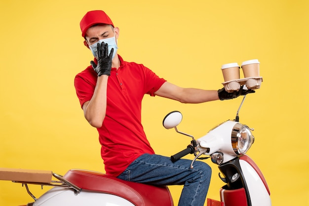 Front view male courier in red uniform and mask with coffee on yellow color job pandemic delivery covid- work food service virus