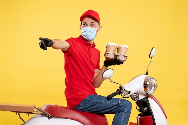 Front view male courier in red uniform and mask with coffee on a yellow color job pandemic delivery covid- work food service