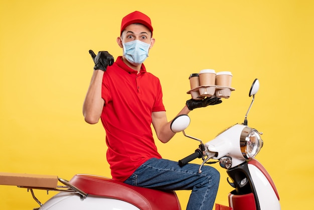 Front view male courier in red uniform and mask with coffee on yellow color job pandemic delivery covid- work food service