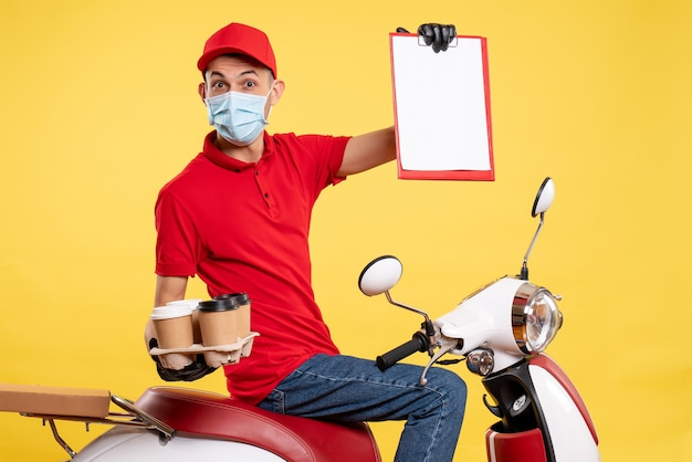Front view male courier in red uniform and mask with coffee on the yellow job pandemic delivery service color covid- work food