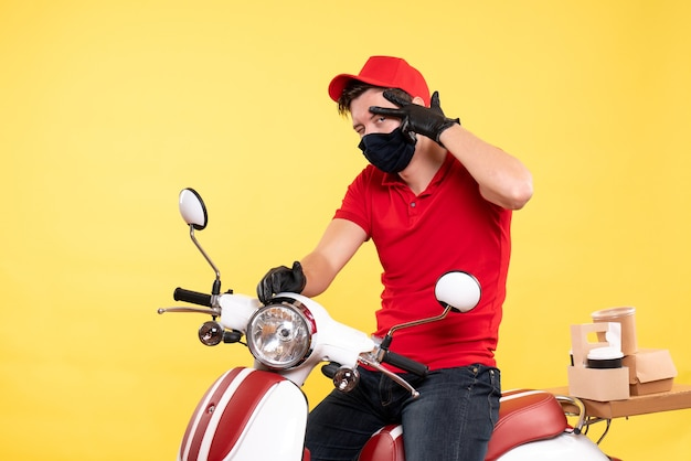 Front view male courier in red uniform and mask on the yellow