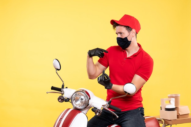 Front view male courier in red uniform and mask on yellow