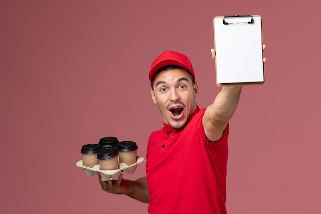 Front view male courier in red uniform rejoicing and holding delivery coffee cups with notepad on pink wall