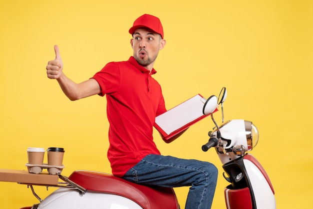 Front view male courier in red uniform with file note on yellow bike color delivery work worker service job