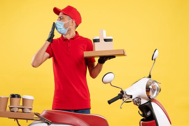 Corriere maschio di vista frontale in uniforme rossa con scatola di cibo e caffè sul servizio di lavoro colore giallo pandemia covid lavoro uniforme virus