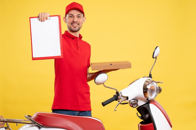 Front view male courier in red uniform with food box on the yellow color delivery worker bike work uniform service job
