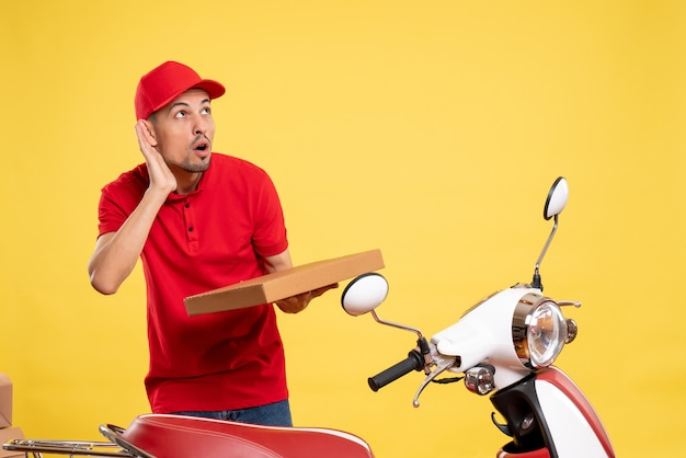 Front view male courier in red uniform with food box on yellow delivery color job worker bike work uniform