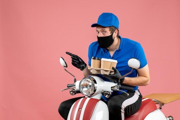 Corriere maschio di vista frontale che si siede sulla bici e che tiene le tazze di caffè sul rosa