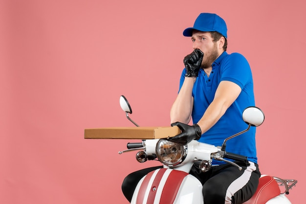 Front view male courier sitting on bike and holding pizza box on a pink