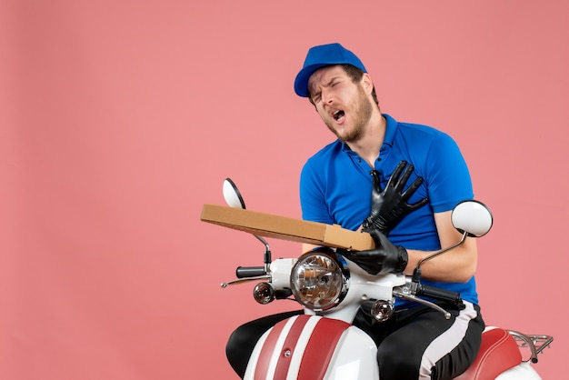 Front view male courier sitting on bike and holding pizza box on pink