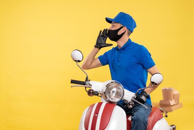 Corriere maschio di vista frontale che si siede sulla bici nella mascherina che chiama qualcuno sul lavoro giallo di servizio di pandemia di consegna covid-uniforme del lavoro
