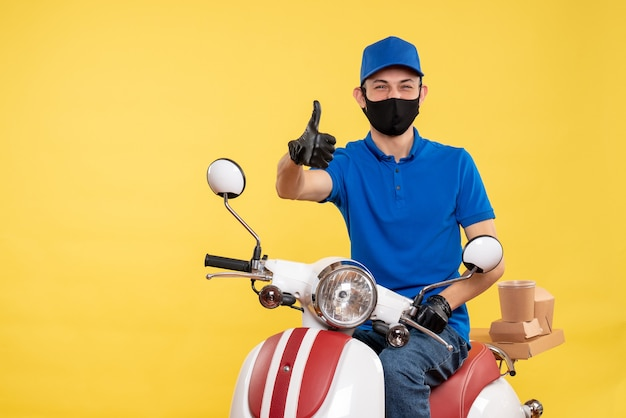 Corriere maschio di vista frontale che si siede sulla bici nella mascherina sulla pandemia di lavoro di covid di consegna del servizio di lavoro giallo
