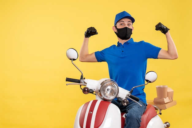 Front view male courier sitting on bike in mask on yellow work service pandemic delivery covid- uniform