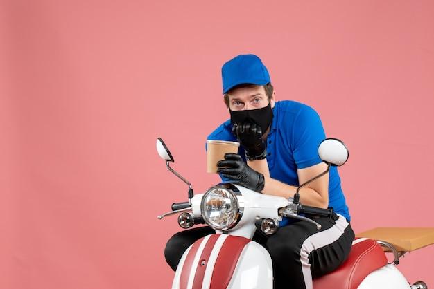 自転車に座って、ピンクのコーヒーを保持している正面の男性宅配便