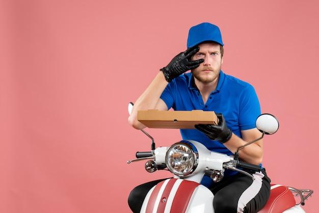 自転車に座って、ピンクのピザの箱を保持している正面の男性宅配便