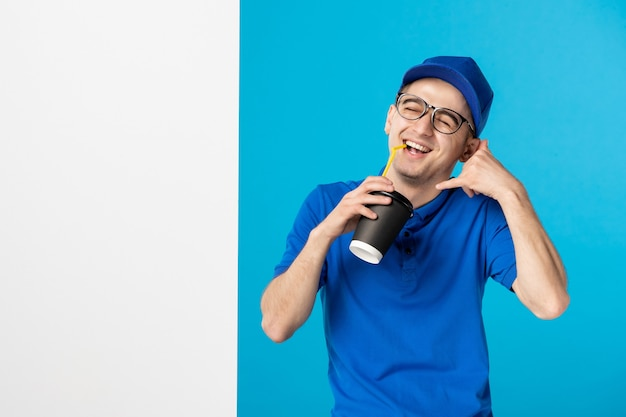Front view male courier in uniform drinking delivery coffee on a blue