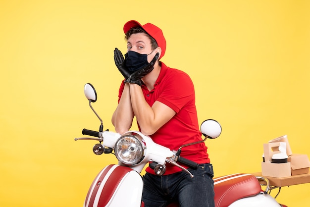 Front view male courier in uniform gloves and mask on yellow