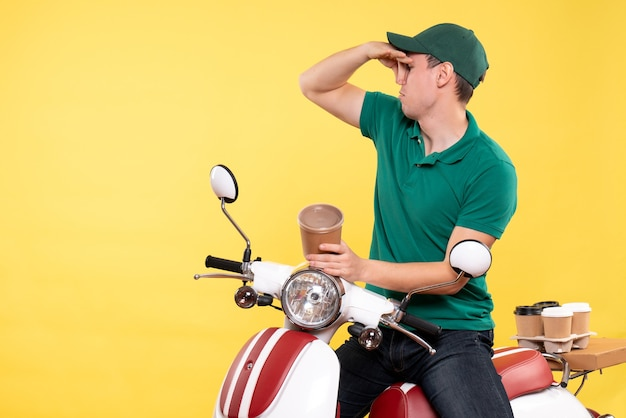Front view male courier in uniform holding coffee cup on the yellow
