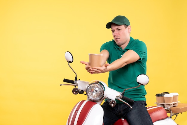 Front view male courier in uniform holding coffee cup on yellow