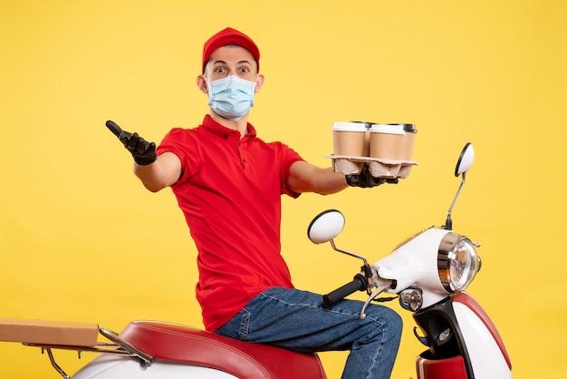 Corriere maschio di vista frontale in uniforme e maschera con caffè sul colore del lavoro di pandemia di lavoro di servizio giallo covid - virus alimentare