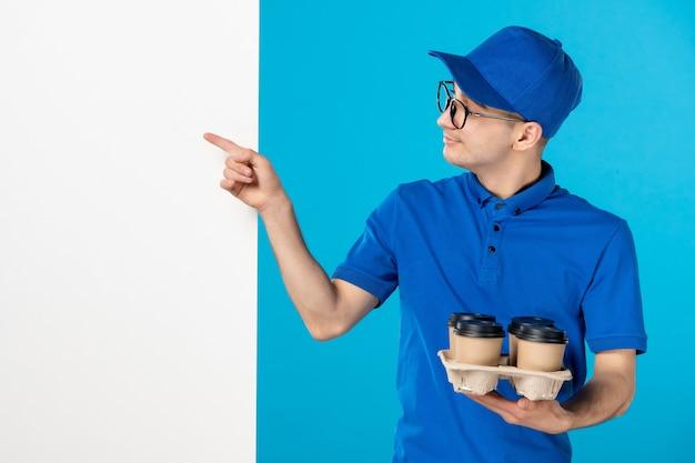 Vista frontale del corriere maschio in uniforme con caffè sull'azzurro