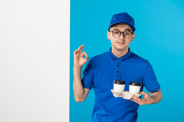 Front view male courier in uniform with coffee on blue