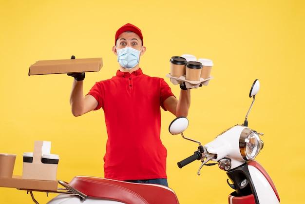 Corriere maschio di vista frontale in uniforme con caffè e scatola di cibo sui colori gialli del virus di lavoro di lavoro di pandemia di servizio covid uniformi