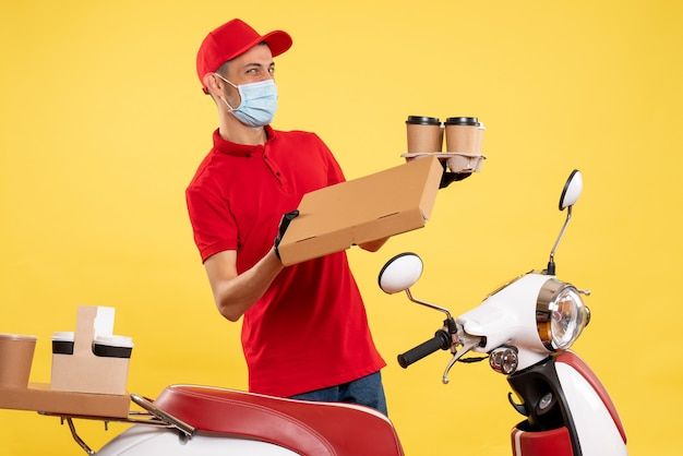 Front view male courier in uniform with coffee and food box on yellow pandemic service work covid uniform job virus