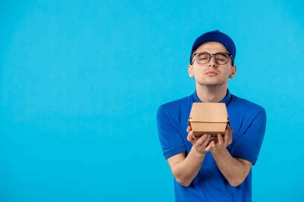 Front view male courier in uniform with food delivery package on blue