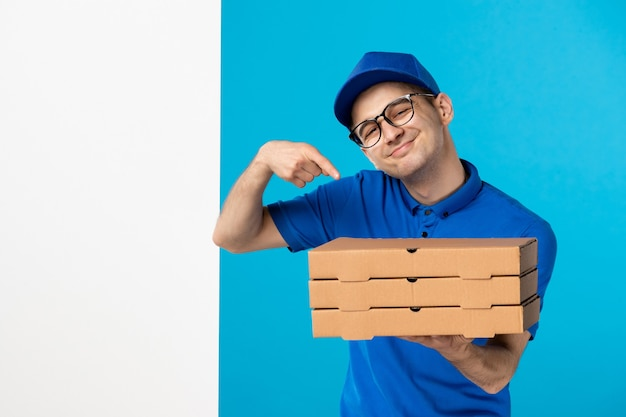 Front view male courier in uniform with pizza boxes on the blue