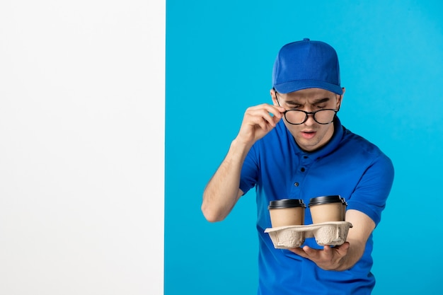 Front view male courier with coffee on blue