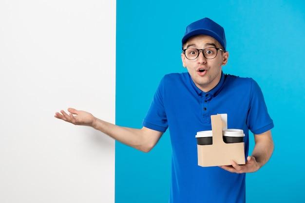 Курьер-мужчина, вид спереди с кофейными чашками на синем