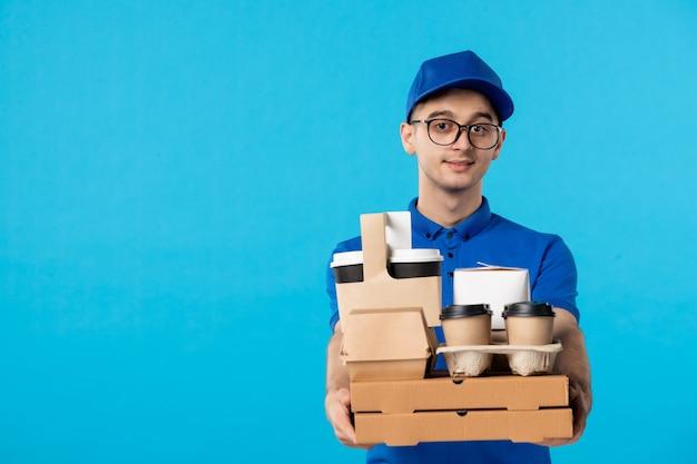 Vista frontale del corriere maschio con scatole di cibo e caffè sull'azzurro