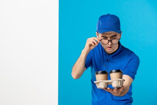 Курьер-мужчина, вид спереди с кофе на синем