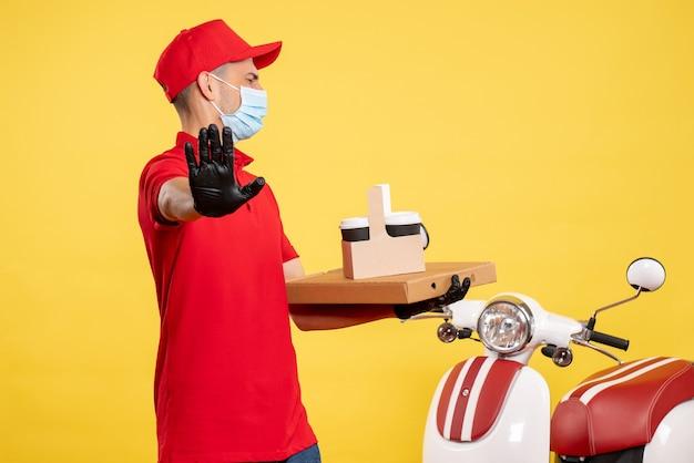 Курьер-мужчина, вид спереди, с доставкой кофе и коробкой, недоволен пандемией желтой рабочей одежды