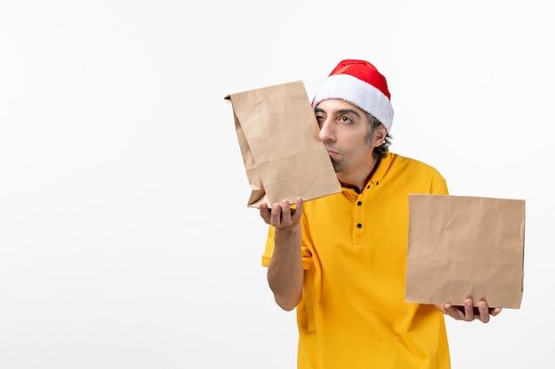 白い床の仕事の食事の制服サービスの食品パッケージと正面図の男性の宅配便
