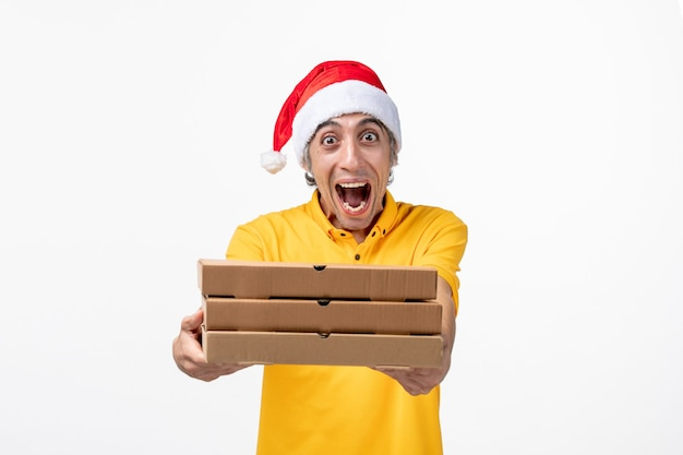白い壁の制服配達サービスの仕事にピザの箱と正面図の男性の宅配便