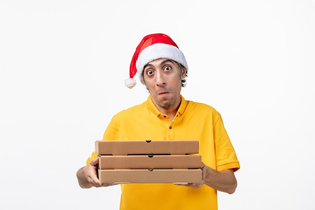 明るい白い机の上のピザの箱が付いている正面図の男性の宅配便仕事の均一な配達サービス