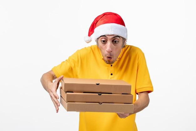 Вид спереди мужской курьер с коробками для пиццы на белой стене рабочая форма службы новый год