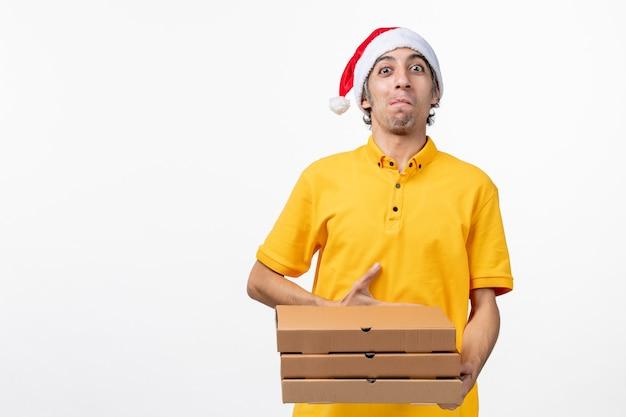 白い机の上のピザの箱が付いている正面図の男性の宅配便仕事サービス配達制服