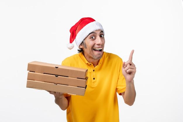 白い机の上のピザの箱が付いている正面図の男性の宅配便仕事の均一なサービスの配達