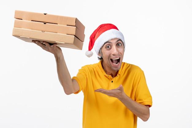 白い机の上のピザの箱が付いている正面図の男性の宅配便制服配達サービス
