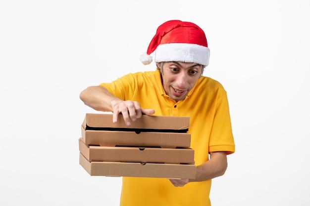 Вид спереди мужской курьер с коробками для пиццы на белом столе, рабочая служебная форма, новый год