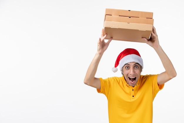白い壁の仕事の制服の配達サービスでピザの箱と正面図の男性の宅配便