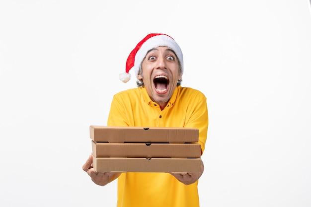 Курьер-мужчина с коробками для пиццы на белой стене, вид спереди, униформа, доставка услуг