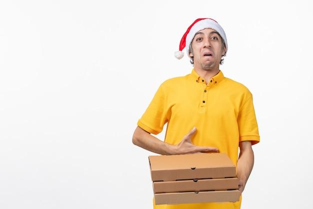 Corriere maschio di vista frontale con scatole di pizza sull'uniforme di consegna di servizio di lavoro della parete bianca