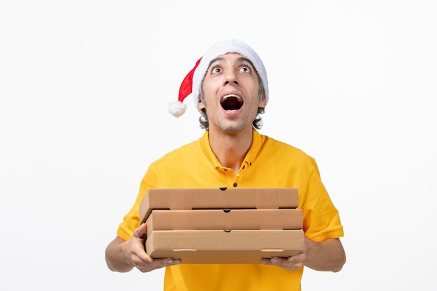 Corriere maschio vista frontale con scatole per pizza sul servizio di consegna uniforme di lavoro muro bianco