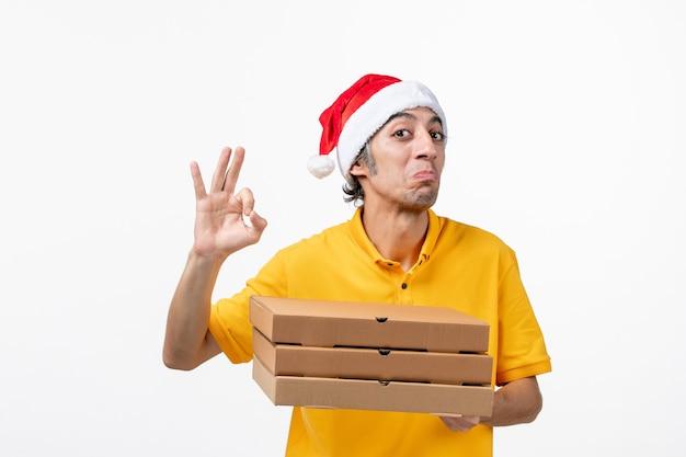 Corriere maschio di vista frontale con scatole di pizza sull'uniforme di lavoro di consegna di servizio della parete bianca