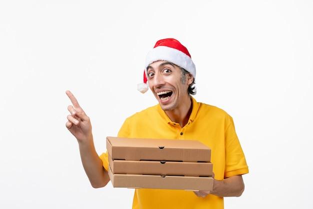 Corriere maschio vista frontale con scatole per pizza sul lavoro di consegna uniforme servizio parete bianca
